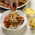 Place 3/4 cup hot rice in each of 4 soup bowls. Top each with 1/4 of steak mixture and 2 tablespoons each cheese and crushed chips.