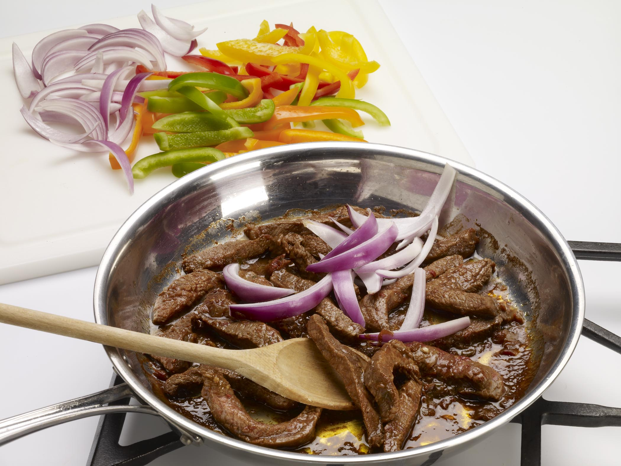 In a skillet, heat oil over medium-high heat.  Remove steak from marinade (discard marinade) and add steak to skillet.  Cook the steak for 3-4 minutes.  Add bell peppers and onion.