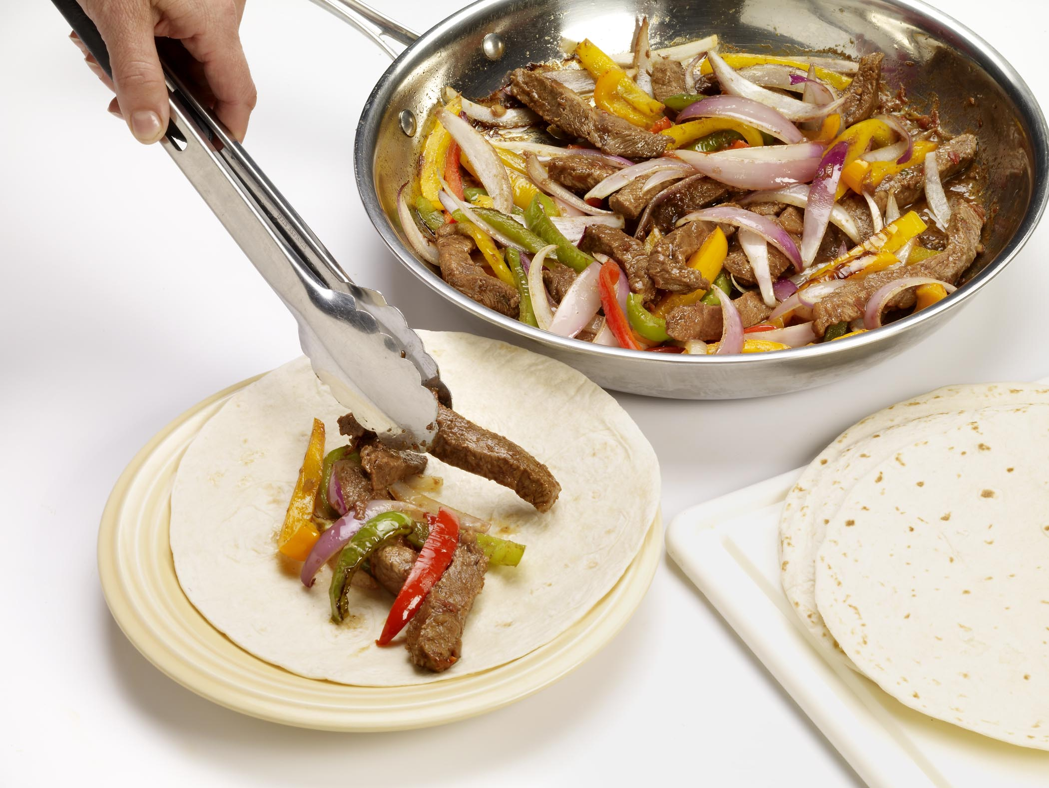 Cook until vegetables are crisply-tender, about 3 additional minutes.  Spoon meat mixture down the center of each tortilla.