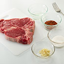 Heat grill to MEDIUM-HIGH. Place garlic, sugar, seasoning and oil in small bowl. Mash with fork to form a paste. Rub evenly onto steaks.