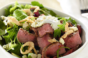 Arrange about 2 cups mixed greens on each of 4 dinner plates. Top with thinly sliced grilled steak. Sprinkle with blue cheese and crispy French Fried onions. Serve with blue cheese or ranch dressing.