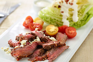 Cut 1 head iceberg lettuce into fourths. Place 1 wedge on each plate. Top with thinly sliced grilled steak, cherry tomatoes, real bacon bits and blue cheese crumbles. Serve with blue cheese or ranch dressing.