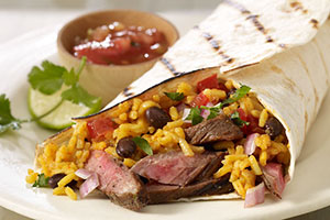 Arrange cut grilled steak on tortillas. Top each with Mexican-style rice and beans, onions, cilantro, salsa and fresh squeezed lime.