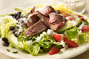 Arrange about 2 cups chopped romaine on each of 4 large plates. Top with black beans, avocado, tomatoes, onions, cilantro, shredded Mexican-style cheese and cut grilled steak. Serve with chipotle ranch dressing.