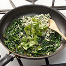 Melt butter in large nonstick skillet on MEDIUM.  Add onions and garlic.  Cook 1 to 2 minutes until tender.  Add spinach.  Cook until slightly wilted, about 3 minutes.  Remove from heat.  Stir in blue cheese and basil.
